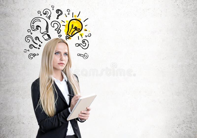 Blond kvinna med en förskriftsbok, frågor, kula arkivbild