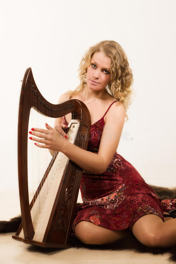Blond kvinna med en harpa i hans hand royaltyfri fotografi