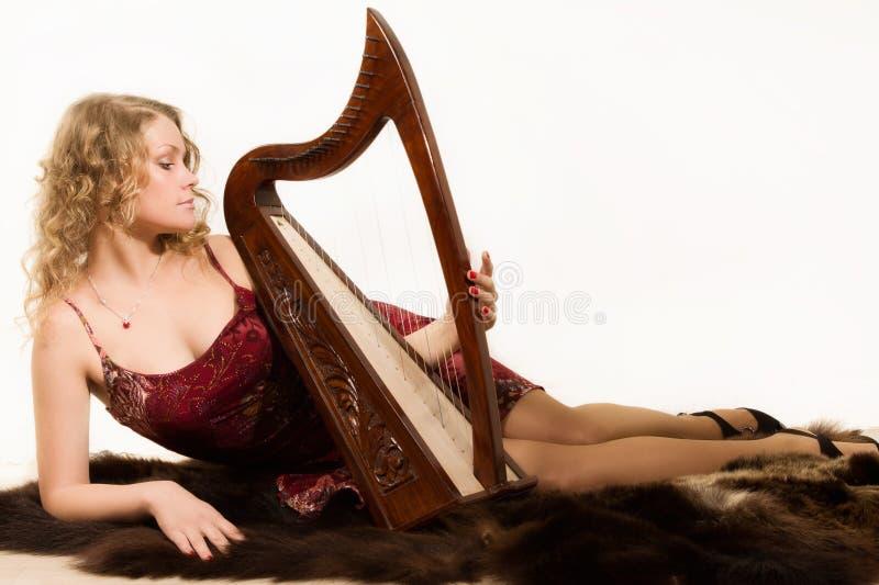 Blond kvinna med en harpa i hans hand arkivbild