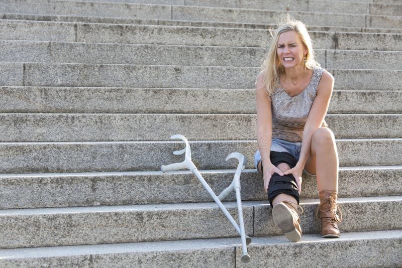 Blond kvinna med kryckor arkivfoto