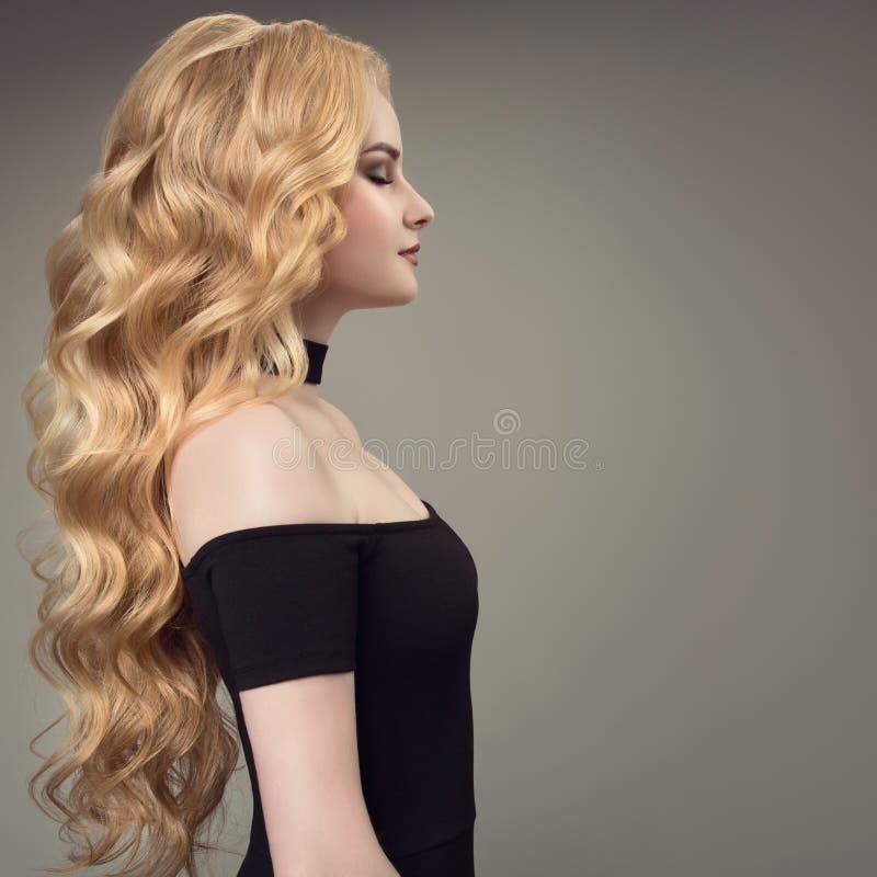 Blond kvinna med långt lockigt härligt hår arkivfoto