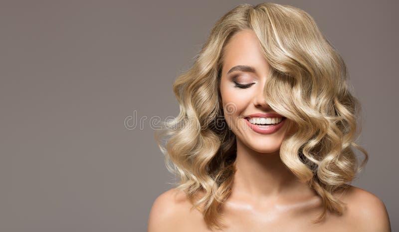 Blond kvinna med lockigt härligt le för hår arkivfoto