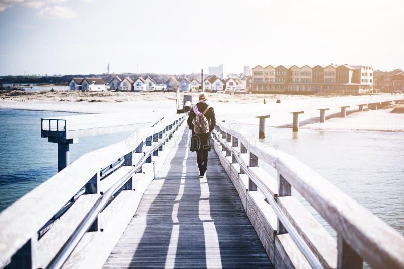 Blond kvinna med ryggsäcken som går på träpir på havet arkivfoton