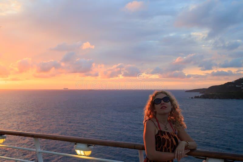 Blond kvinna med solglasögon och sikt av St Maarten i karibiskt royaltyfri fotografi