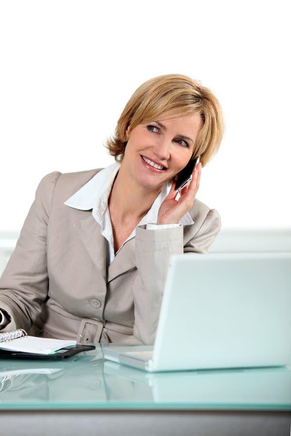 Blond kvinna med telefonen arkivbild