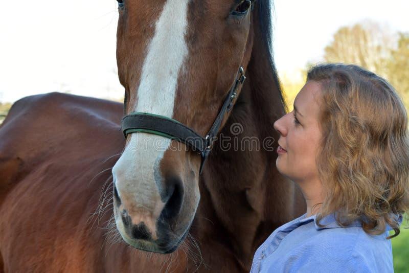 Blond kvinna och hennes häst royaltyfria foton