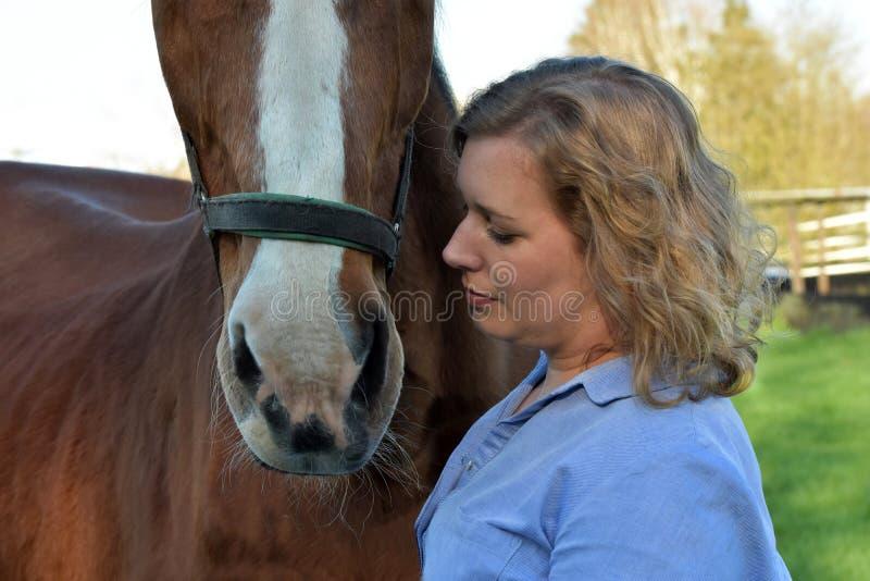 Blond kvinna och hennes häst royaltyfri foto