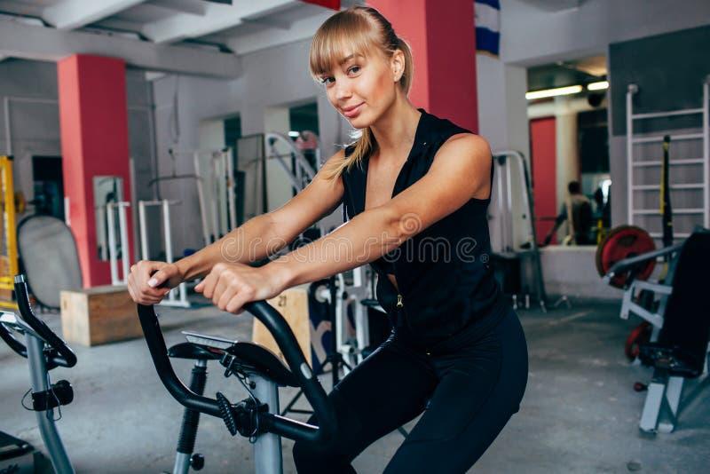 Blond kvinna på den exersizing cykeln royaltyfria bilder