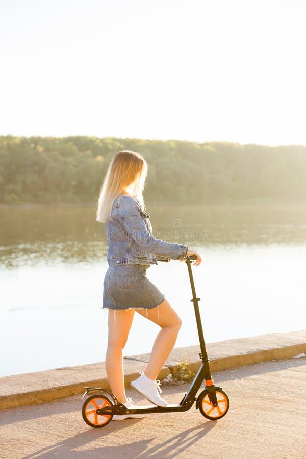 Blond kvinna på en sparkcykel på stranden på solnedgången arkivbild