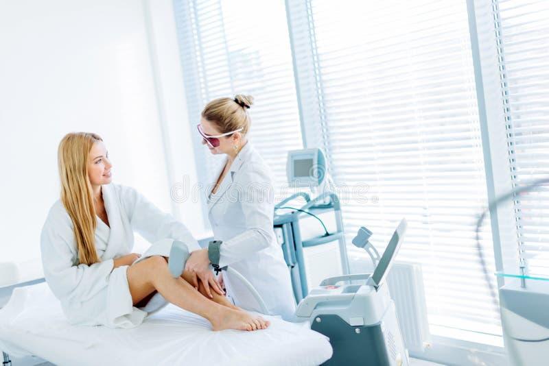 Blond kvinna på tillvägagångssätt för hårborttagningscosmetology Laser-epilationbegrepp royaltyfria bilder