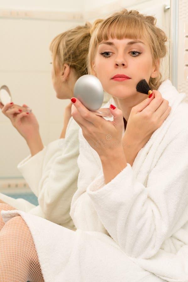 Blond kvinna som använder mascaraborsten i badrum arkivbilder