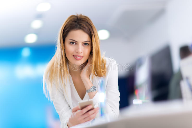 Blond kvinna som använder på den smarta telefonen i lager royaltyfria bilder