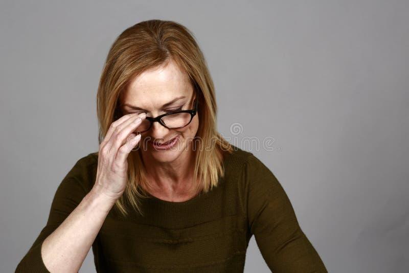 Blond kvinna som av tar hennes exponeringsglas royaltyfria bilder