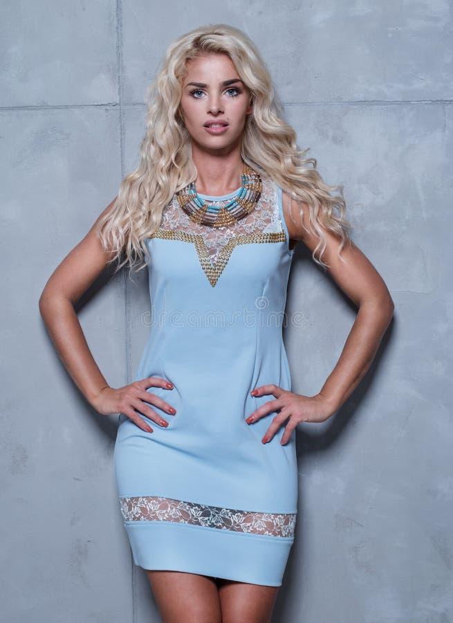 Blond kvinna som bär den stilfulla blåttklänningen royaltyfria bilder