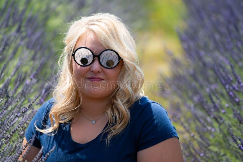 Blond kvinna som bär googly ögonkrimskramssolglasögon, medan sitta i ett fält av lavendel arkivfoto