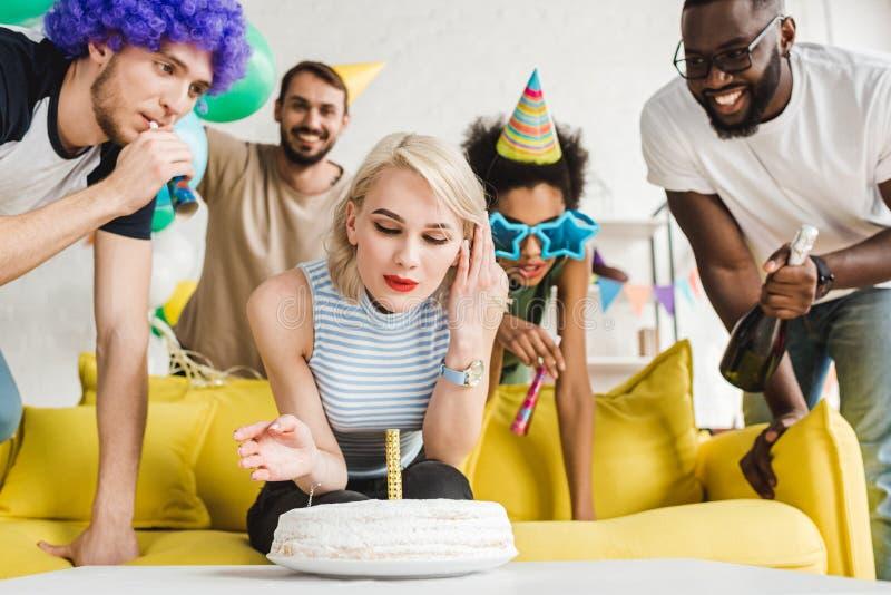 Blond kvinna som blåser stearinljuset på födelsedagkakan av henne fotografering för bildbyråer
