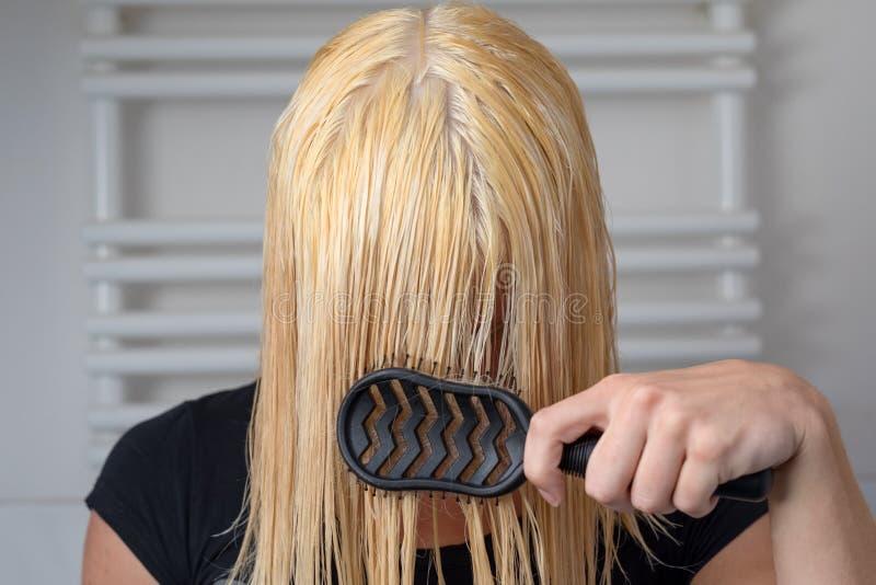Blond kvinna som borstar till och med hennes långa våta hår royaltyfria foton