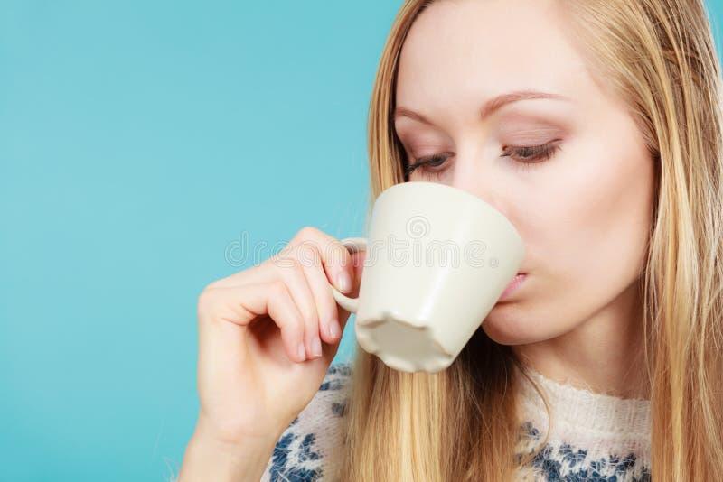Blond kvinna som dricker den varma drinken från koppen arkivfoto