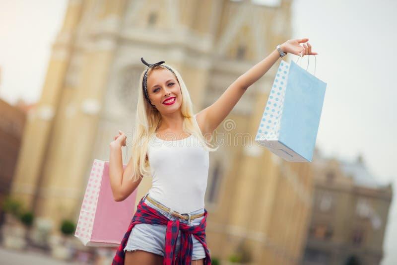 Blond kvinna som går med shoppingpåsar royaltyfri foto