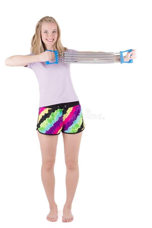 Blond kvinna som gör övningar med expanderen arkivbild