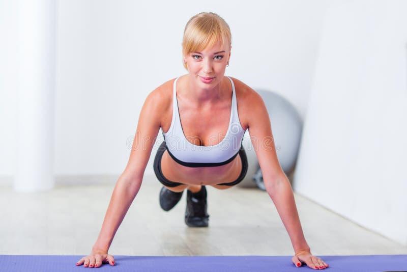 Blond kvinna som gör push-UPS royaltyfri fotografi