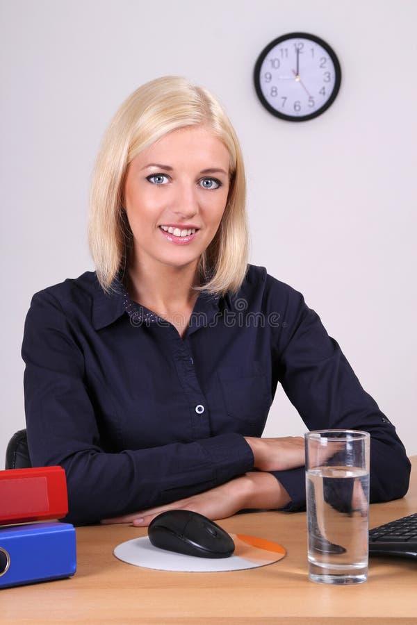 Blond kvinna som i regeringsställning sitter royaltyfri fotografi