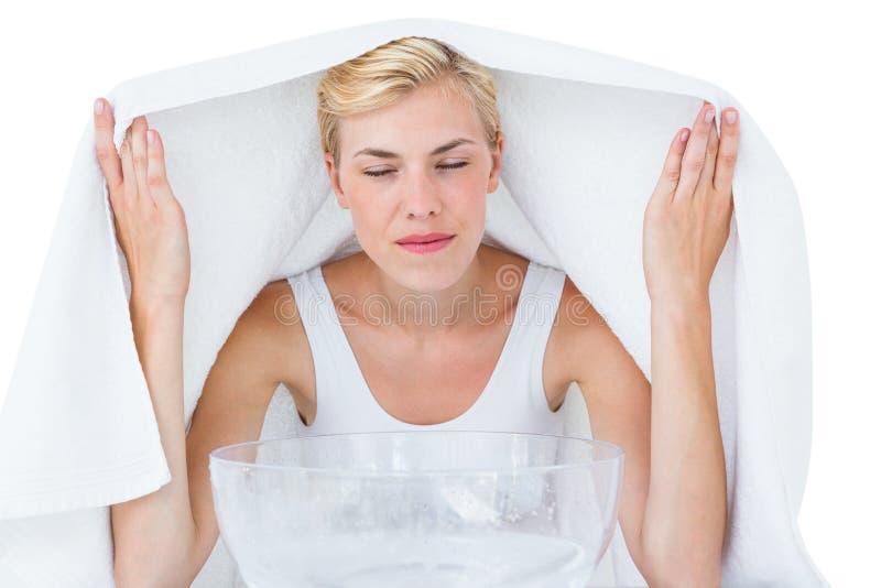 Blond kvinna som inhalerar växt- medicin royaltyfria foton