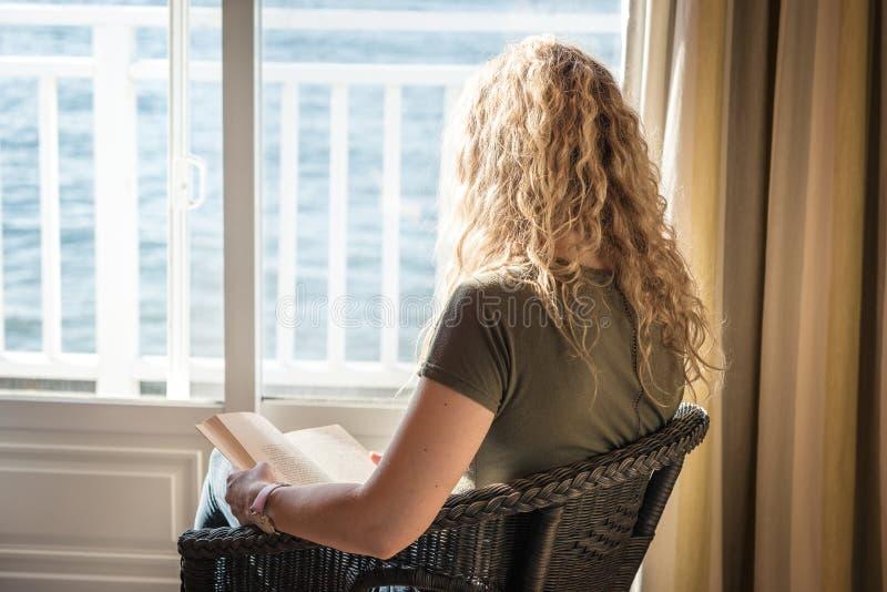 Blond kvinna som läser en bok framför havet royaltyfri bild