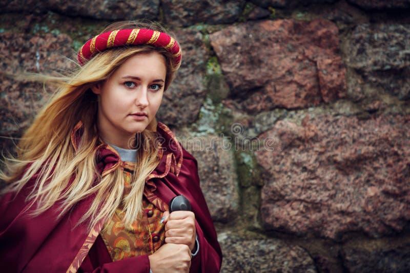 Blond kvinna som poserar att stå med svärdet i röd kläder arkivfoto