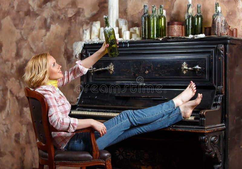 Blond kvinna som poserar i fåtölj med den vaxade vinflaskan arkivbild