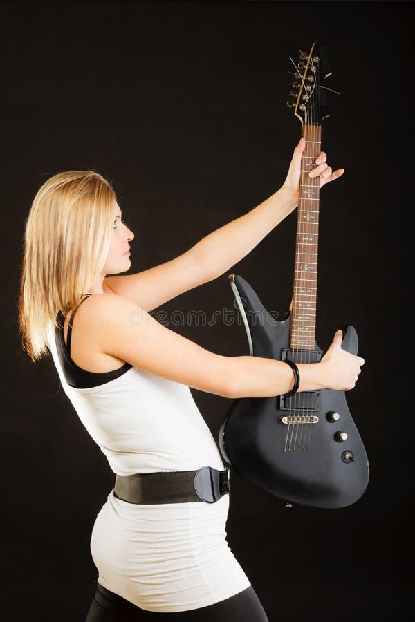 Blond kvinna som rymmer den elektriska gitarren, svart bakgrund arkivfoton