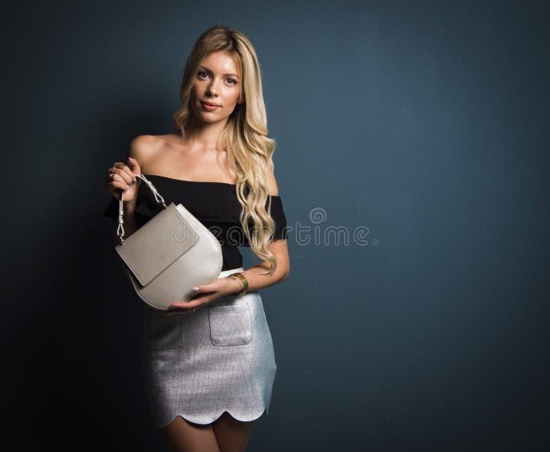 Blond kvinna som rymmer den lilla handväskan på mörkt - grå bakgrund royaltyfri foto