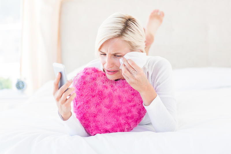 Blond kvinna som rymmer hennes mobiltelefon och gråt arkivfoton