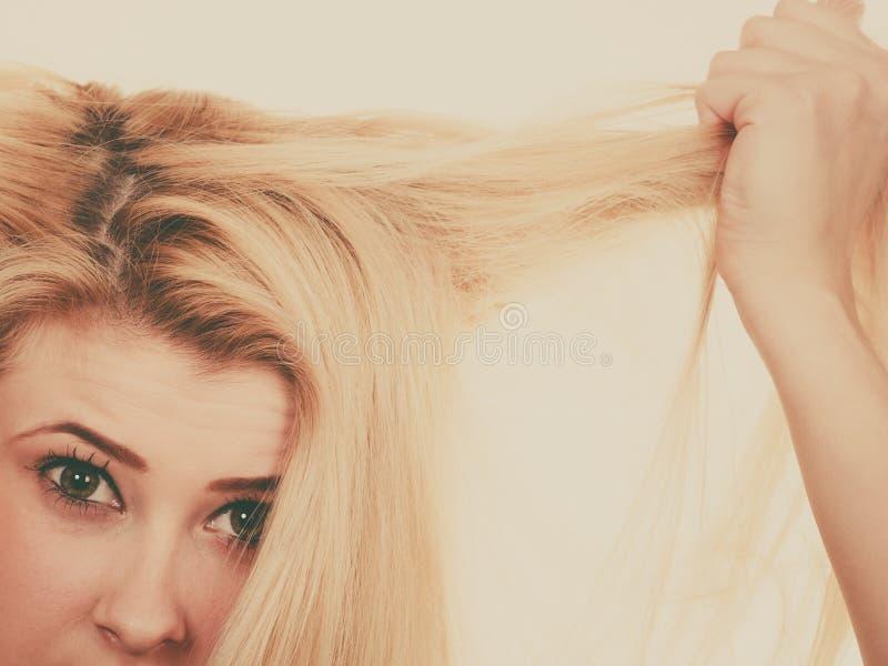 Blond kvinna som rymmer hennes torra hår fotografering för bildbyråer
