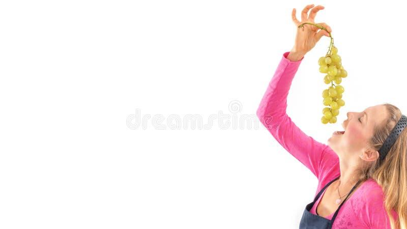 Blond kvinna som rymmer mogna druvor, vit bakgrund arkivbilder
