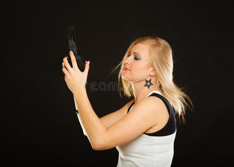Blond kvinna som rymmer stor hörlurar i studio arkivbild