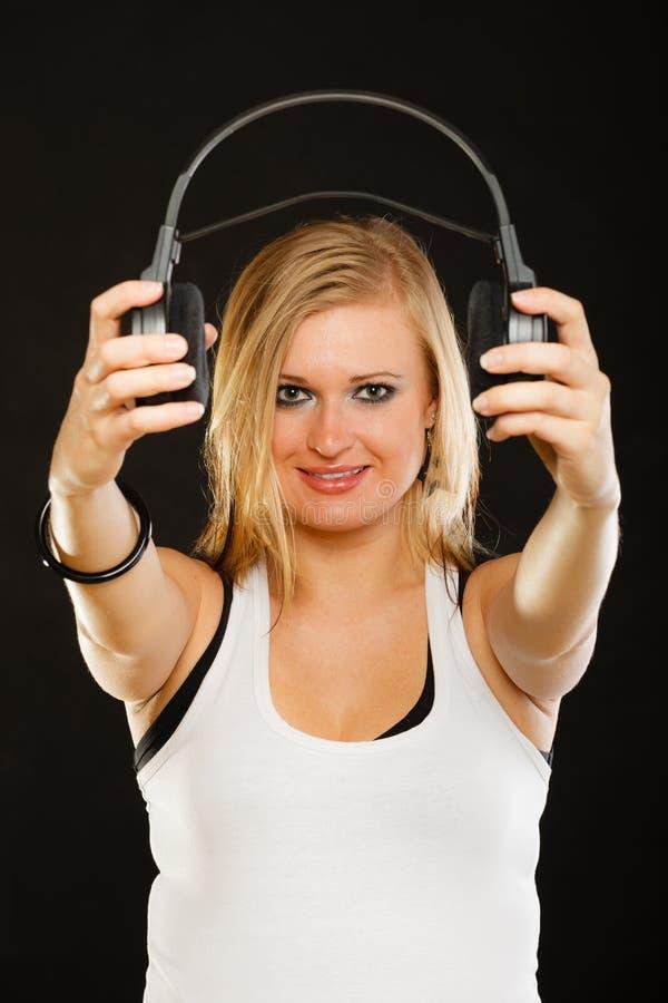 Blond kvinna som rymmer stor hörlurar i studio fotografering för bildbyråer