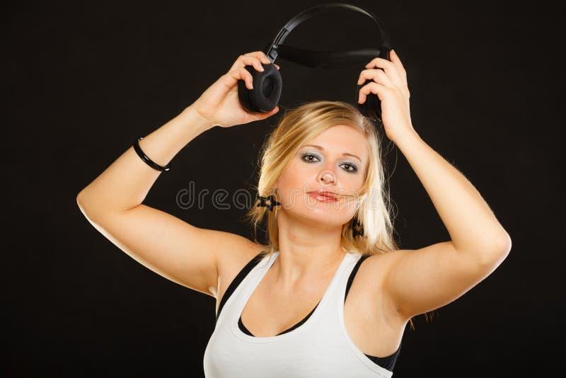 Blond kvinna som rymmer stor hörlurar i studio royaltyfri foto
