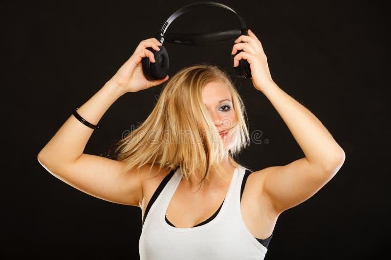 Blond kvinna som rymmer stor hörlurar i studio royaltyfria foton
