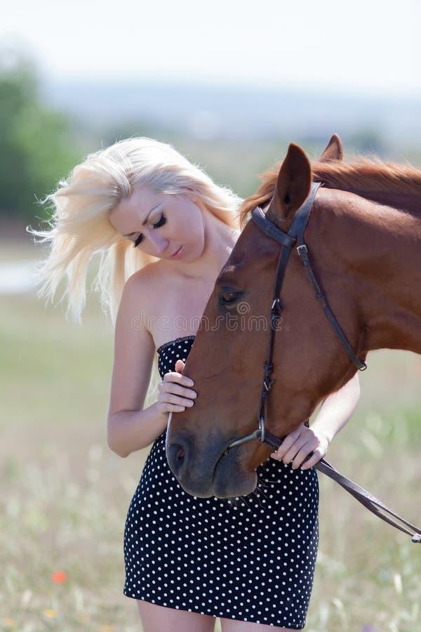 Blond kvinna som slår hästen arkivfoto