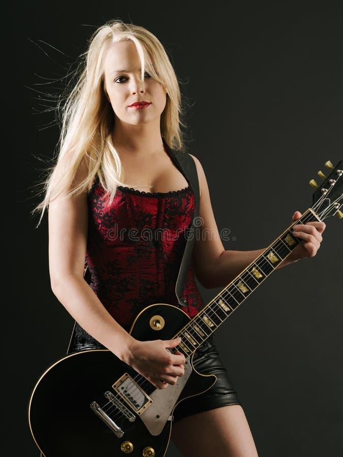 Blond kvinna som spelar den elektriska gitarren arkivfoto