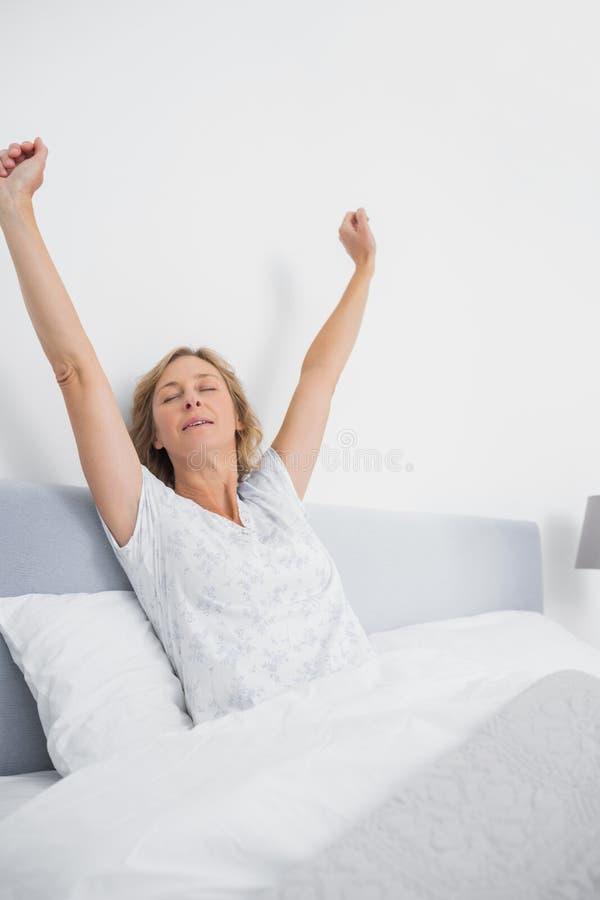 Blond kvinna som sträcker i säng i morgonen arkivbild