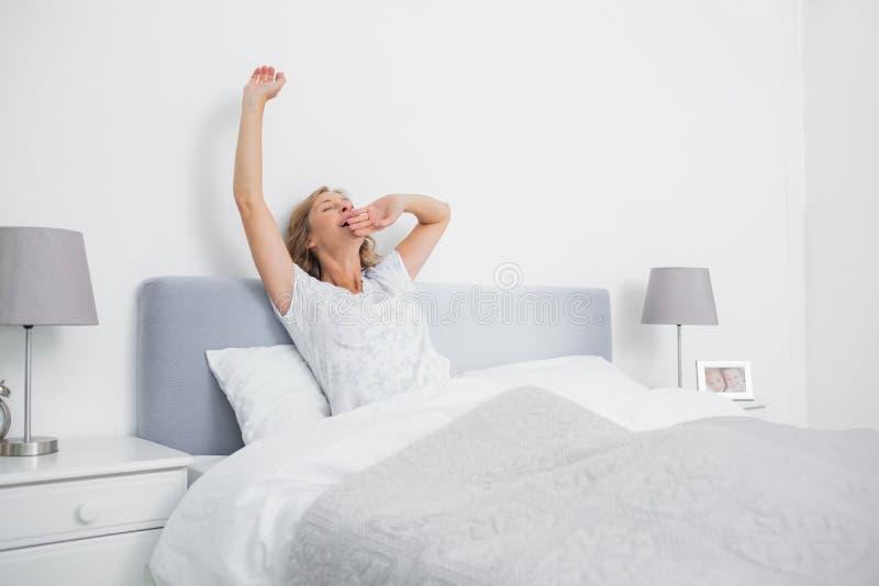 Blond kvinna som sträcker och gäspar i säng i morgonen fotografering för bildbyråer