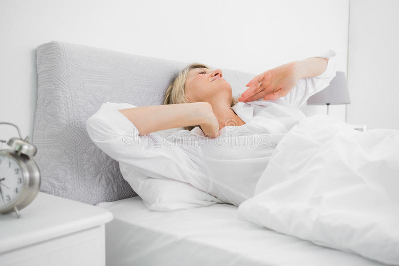 Blond kvinna som sträcker och vaknar upp arkivfoton