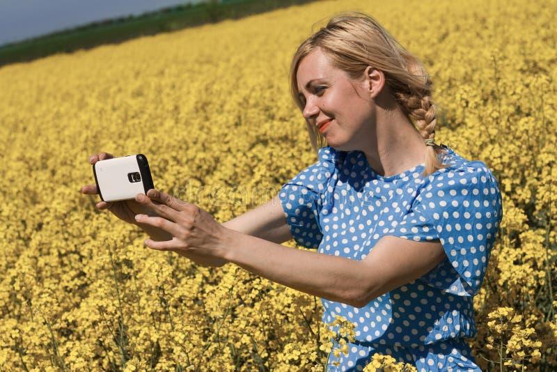 Blond kvinna som tar en selfie i ett canolafält arkivbilder