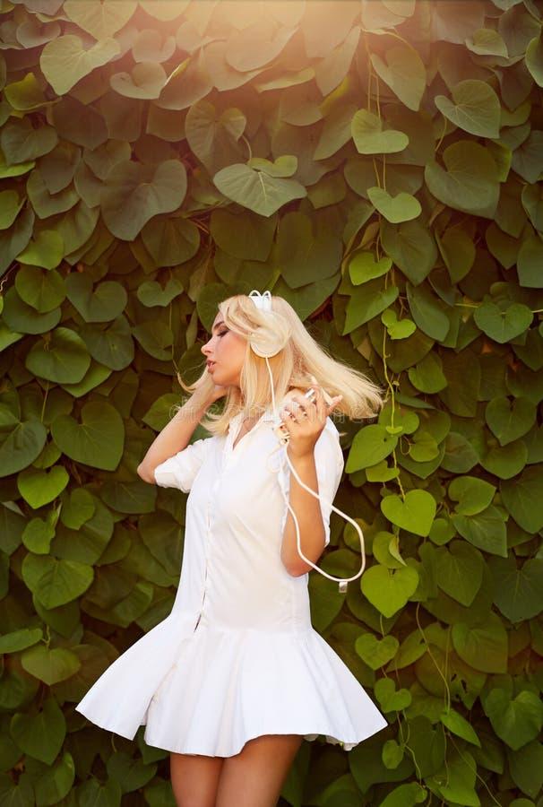 Blond kvinnadans i sidor för en gräsplan, medan lyssna till musik royaltyfri bild