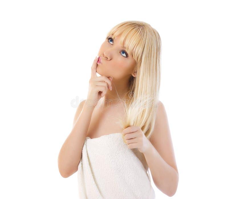 Blond kvinnaholding henne hår och tänka royaltyfria foton