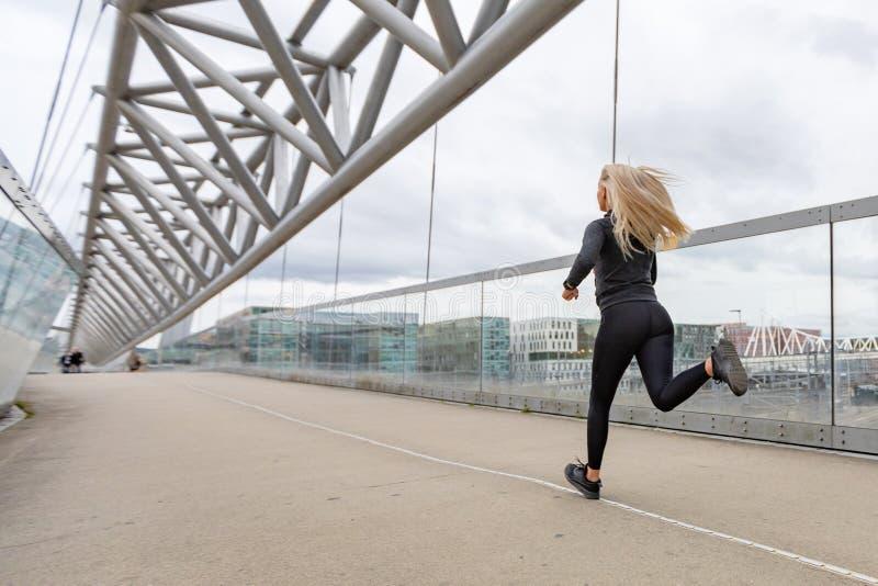 Blond kvinnalöpare i svart genomköraredräkt i modern stadsmiljö arkivfoto