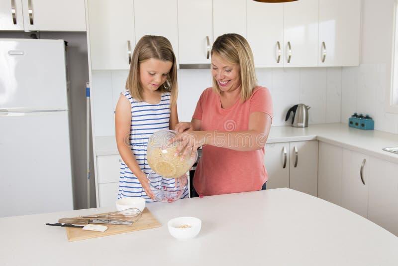 Blond kvinnamatlagning och bakning som är lyckliga samman med hemmastatt kök för söt förtjusande mini- kockliten flicka i moder-  royaltyfria foton