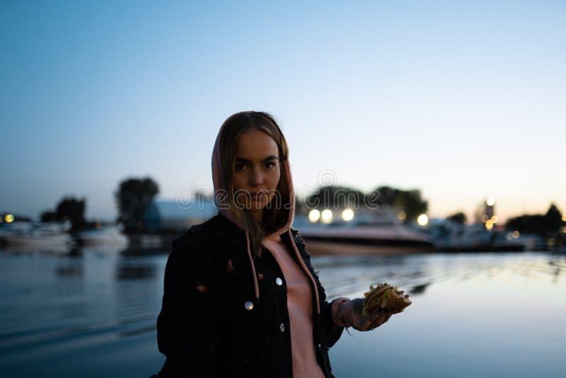 Blond kvinnastående som äter bärande exponeringsglas för hamburgare som står vid floden på natten royaltyfri bild